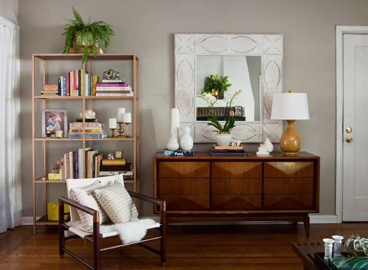 O aparador de madeira ainda continua sendo o mais escolhido na hora de decorar a casa. Para diferenciar, você pode optar por um espelho de moldura mais caprichada.