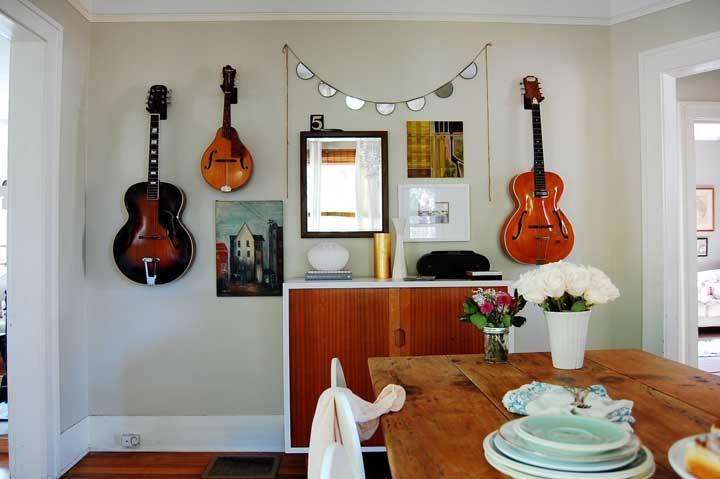 Para os amantes de música, use o aparador para colocar alguns objetos de decoração e reserve a parede para pendurar seus instrumentos musicais junto com um pequeno espelho.