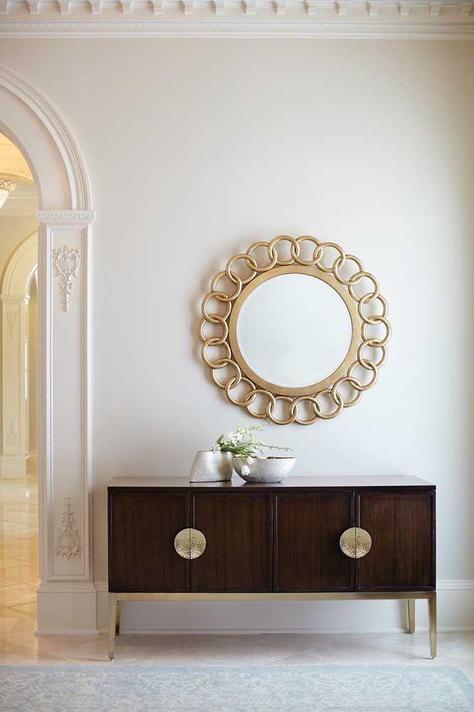A moldura do espelho feita de argola dourada combina perfeitamente com os detalhes em dourado do aparador de espelho feito de madeira.