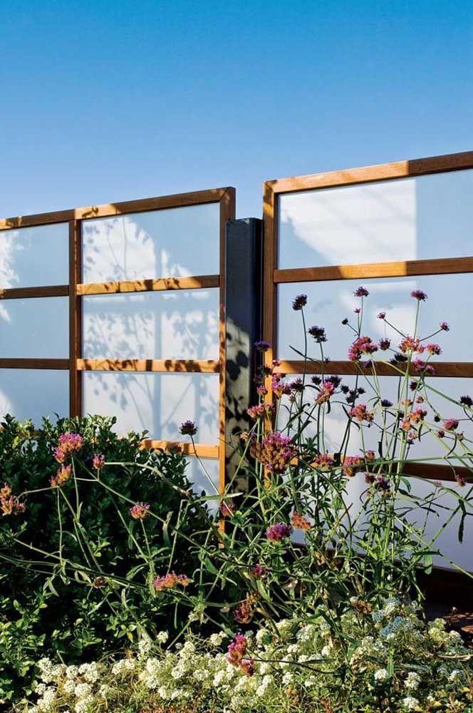 Vidro, aço e madeira se unem para formar esse muro; o vidro leitoso traz a privacidade necessária aos moradores