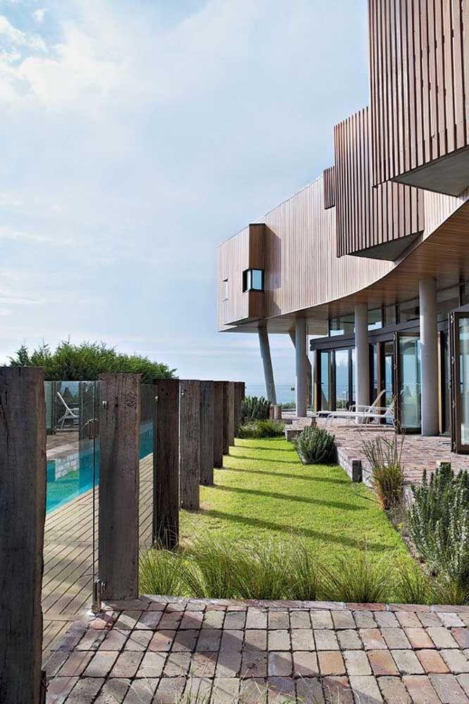 Os troncos rústicos de madeira formam uma combinação inusitada e contrastante com o vidro incolor deixando a fachada da casa levemente rústica, sem perder o apelo moderno