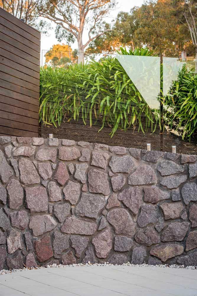 Meio a meio: o muro dessa casa foi construído com pedras brutas na parte de baixo e vidro na parte de cima