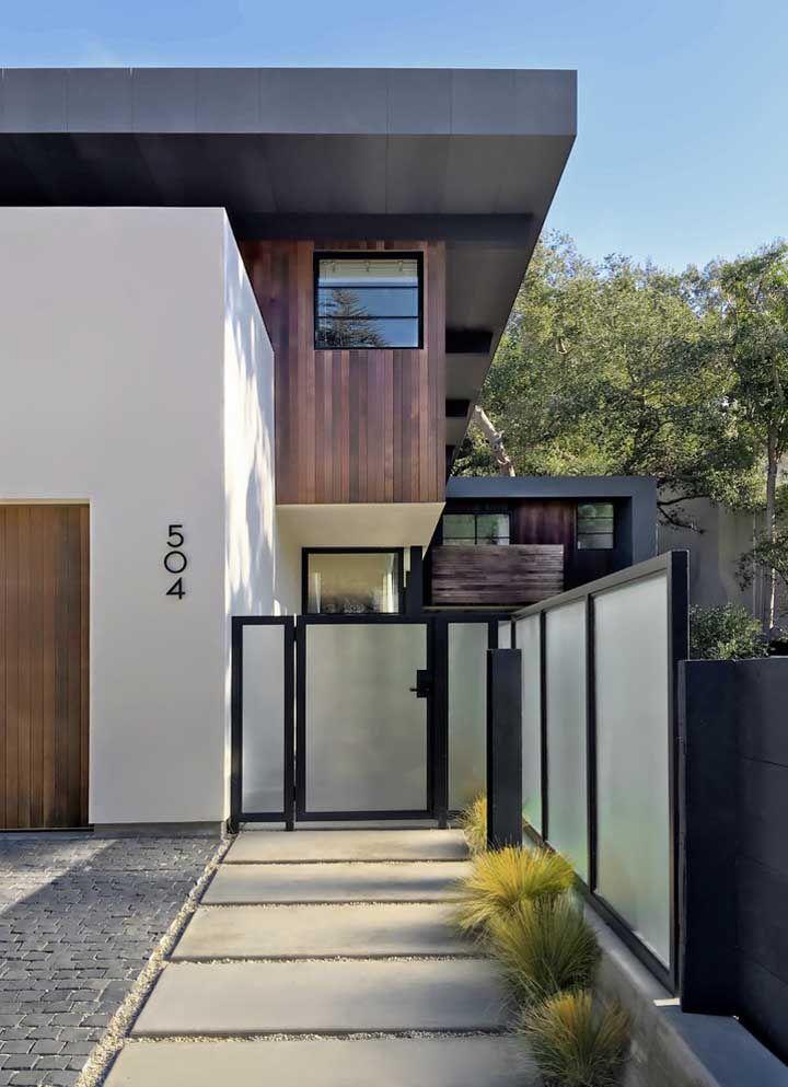 O vidro leitoso branco faz referência direta à cor das paredes da casa; a moldura preta é o detalhe que não poderia faltar