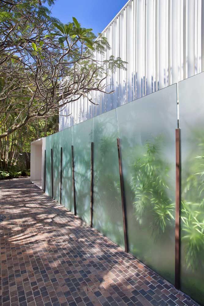 Muro de vidro jateado com detalhes em madeira; o jardim interno pode ser parcialmente visualizado pelo lado de fora