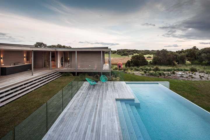 O guarda corpo de vidro protege a área da piscina sem tirar a visão para a casa