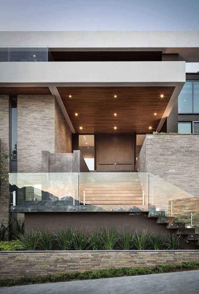 Levemente espelhado, esse muro de vidro traduz a estética moderna e arrojada da casa