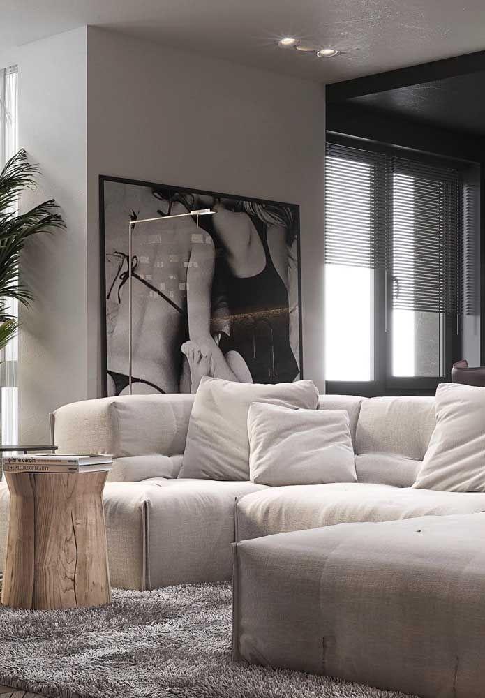 O palha discreto no sofá foi harmonizado com o cinza do tapete, já os detalhes pretos conferem modernidade a sala