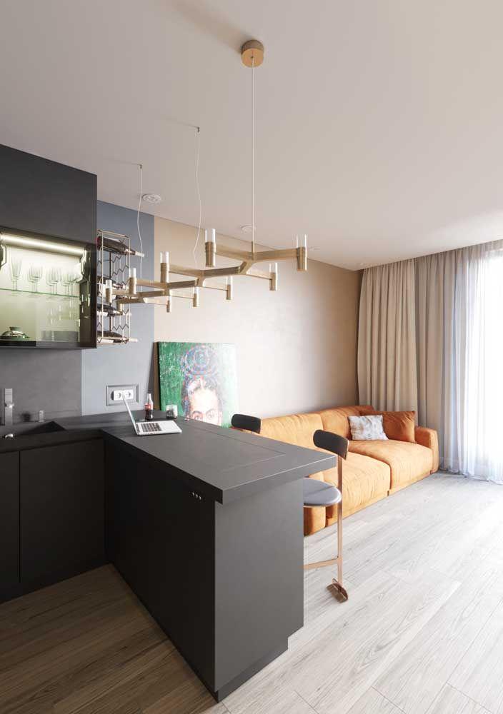 O sofá laranja queimado se harmoniza diretamente com a parede palha, o cinza no ambiente ao lado completa a proposta