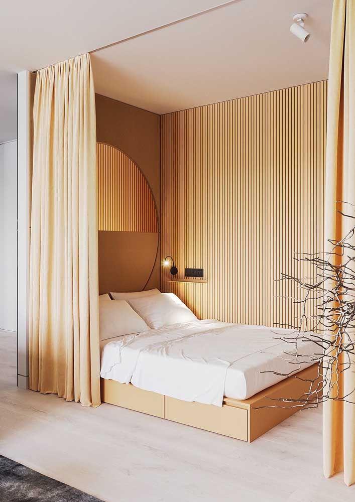 O tom palha mais quente desse quarto ficou super aconchegante com a luminária de luz amarela sobre a cama