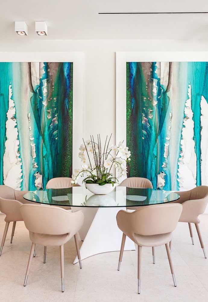 O quadro abstrato em tons de azul e verde força um contraste marcante com o tom de palha