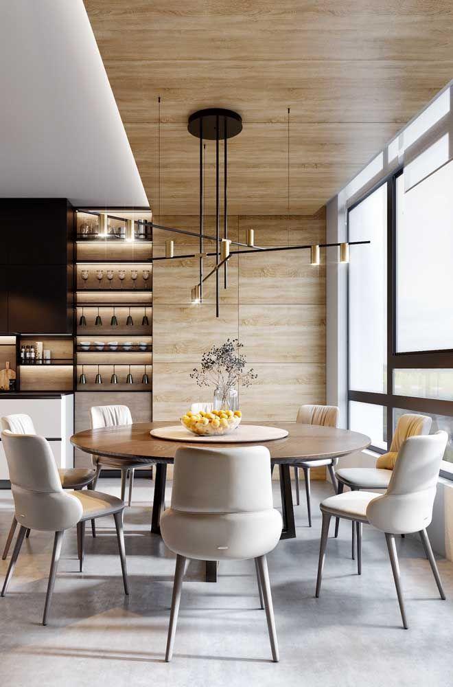 Essa sala de jantar traz a cor palha no estofamento das cadeiras e no revestimento de madeira no teto