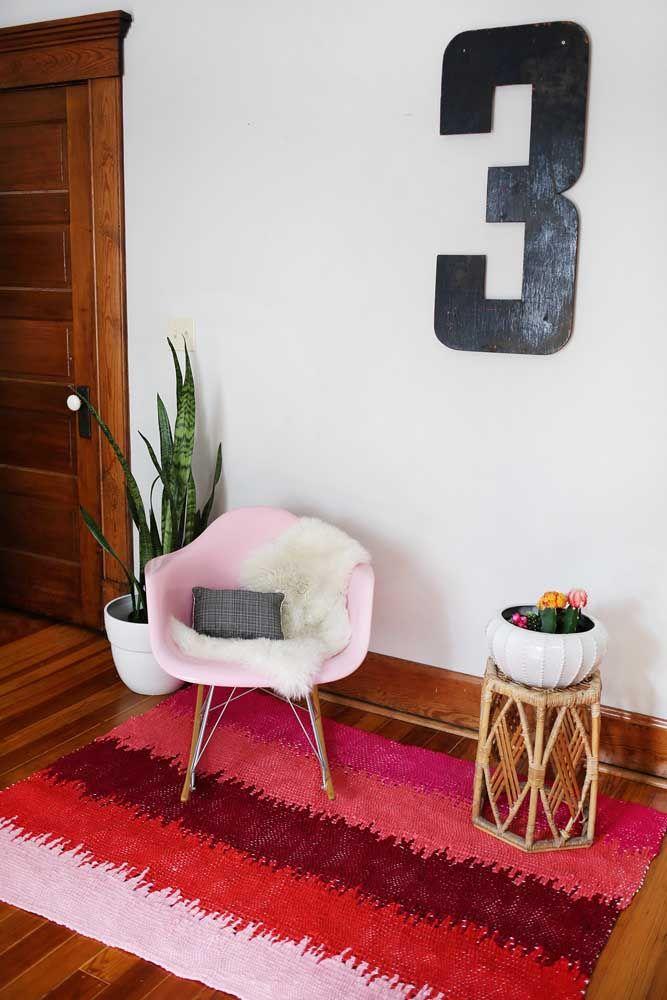 Um cantinho pra lá de acolhedor decorado com tapete de crochê com um vibrante tom sobre tom do vermelho ao rosa