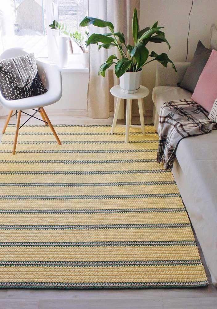 O tapete de crochê de listras amarelas e cinzas cobre toda a extensão da sala