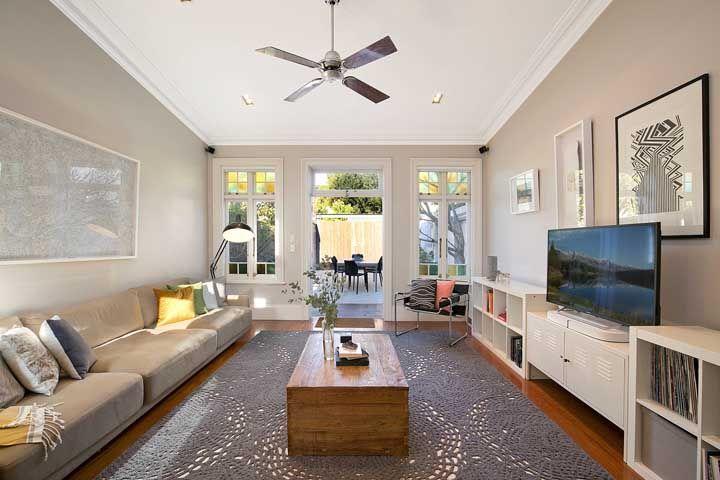 O tapete de crochê cinza e vazado cria uma atmosfera retrô e clássica para essa sala