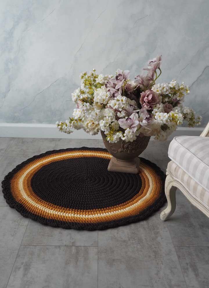 Os tons de marrom e amarelo formam um bonito contraste com o preto do tapete de crochê