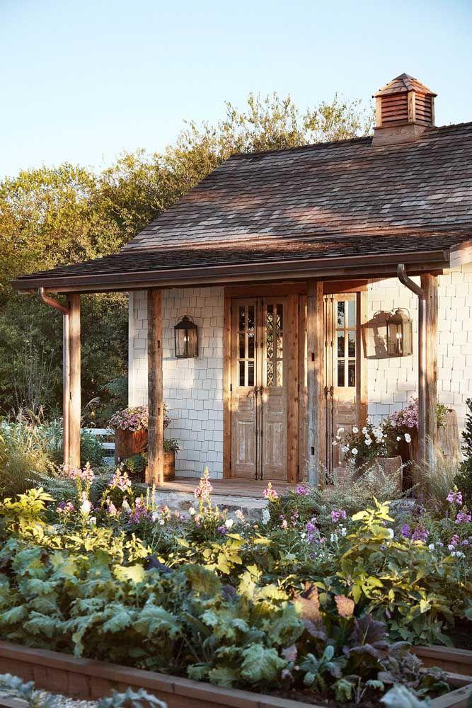Casinha pequena e rústica adornada pelo jardim de frente