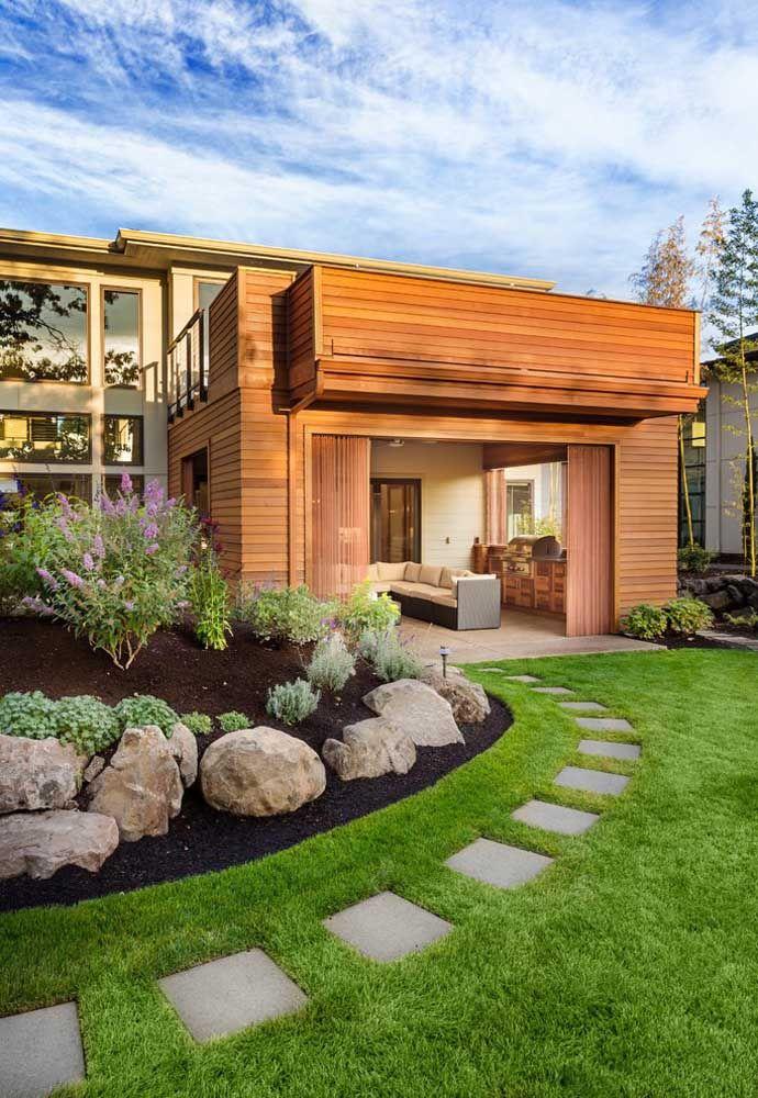 Pedra e grama para ressaltar a beleza da fachada de madeira