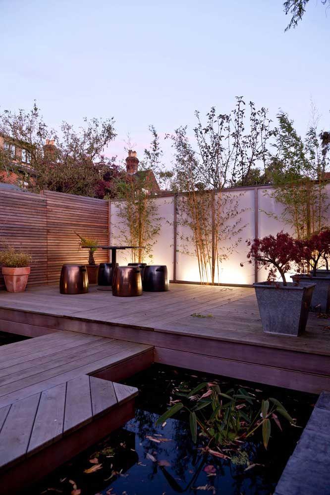 Jardim com mini lago, deck de madeira, vasos, banquinhos e bambus