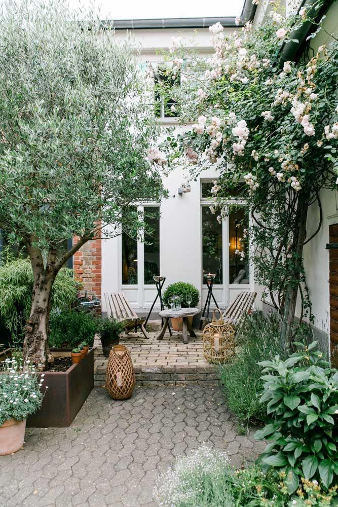 Nessa área externa, o jardim foi criado nas laterais rente ao muro; as árvores fecham o espaço aéreo, garantindo o clima de tranquilidade e aconchego