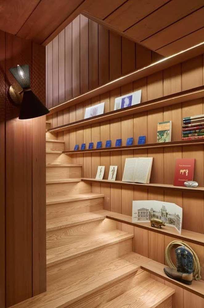 Aqui, a parede da escada também entrou na brincadeira e ganhou prateleiras de madeira por toda sua extensão.