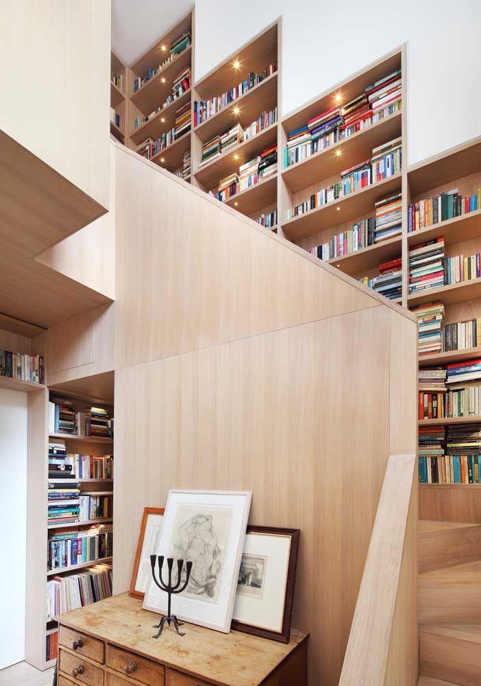 Prateleiras de madeira para livros ao longo da escada