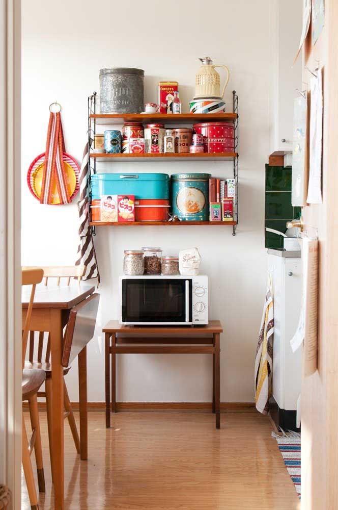 Aqui as prateleiras de madeira ajudam na organização da cozinha pequena que pedia por mais espaço