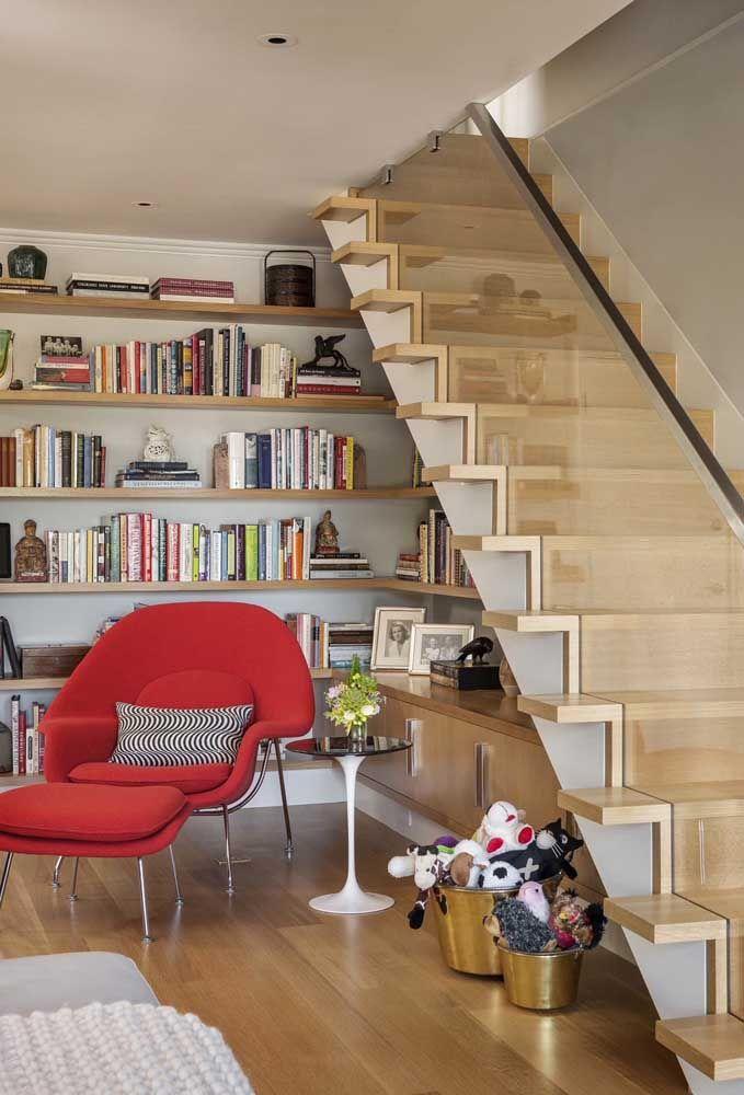O espaço abaixo da escada foi mais que aproveitado com as prateleiras de madeira para livros, montando um lindo cantinho da leitura