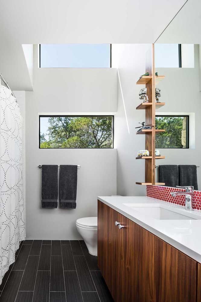 A pequena prateleira de madeira no banheiro ganhou vida com os vasinhos de planta