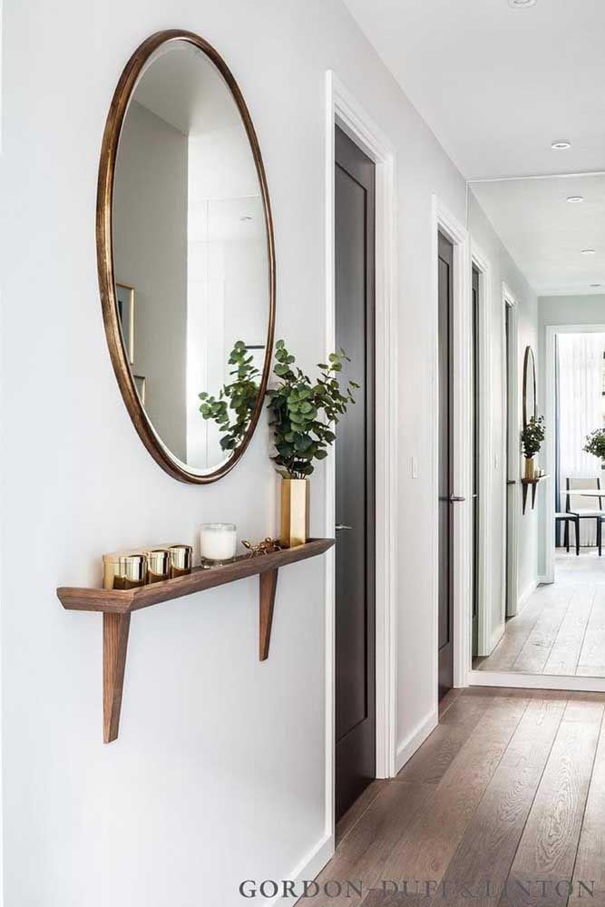 Halls de entrada com pouco espaço podem receber prateleiras de madeira pequenas, ideias para apoiar as chaves, pequenos vasos e outros itens menores