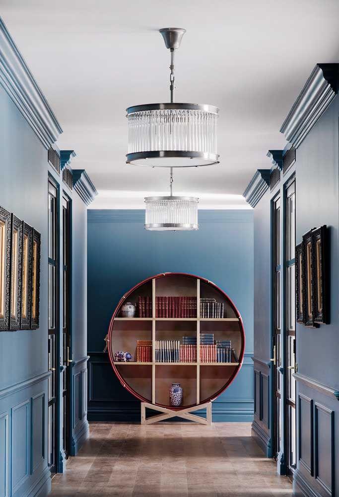 Colocado ao fundo de um corredor, esse nicho grande composto por repartições espaçosas serve como estante para livros, causando impacto na decoração tanto por seu tamanho, quanto pela sua cor