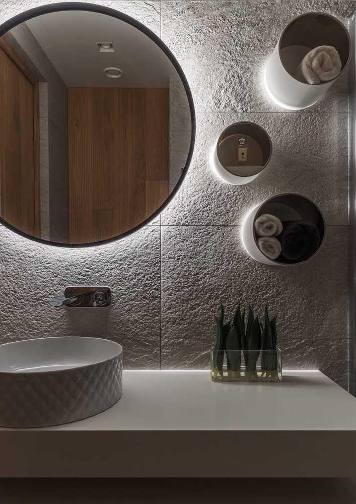Nichos redondos sobre a pia do banheiro servindo como espelho e também porta toalhas e outros objetos; as luzes ao fundo são outro destaque