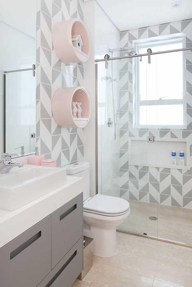 Os nichos cor de rosa com objetos decorativos infantis trazem graça e leveza à decoração deste banheiro