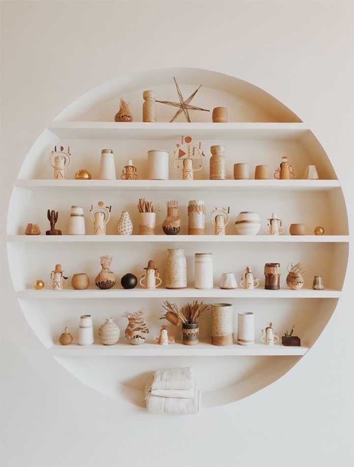 Pequenos objetos de decoração em uma única cor acomodados com cuidado no nicho branco