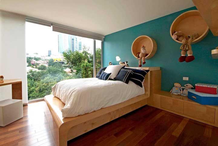 Nesse quarto, os nichos redondos de madeira acompanham a cor da cama e ajudam a causar um belo contraste no ambiente