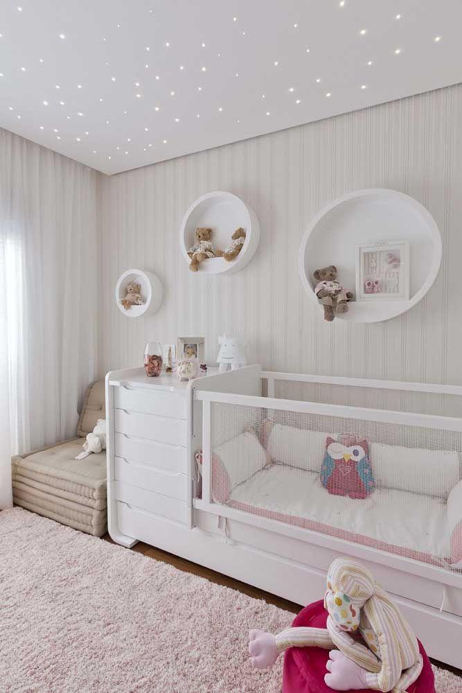 Os nichos redondos brancos no quarto do bebê completam a decoração com uma delicadeza extra