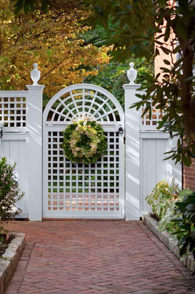 O clássico portão branco demarca a área interna da externa da casa; a continuidade visual fica por conta das pedras no chão