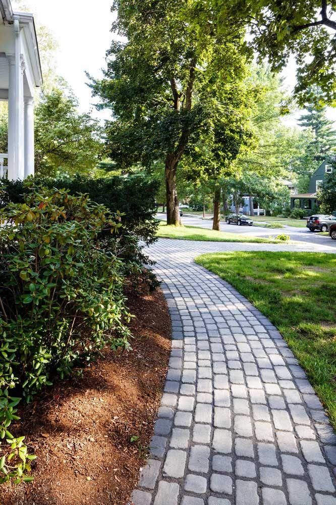Caminho simples de pedra granito valorizado pelo projeto paisagístico