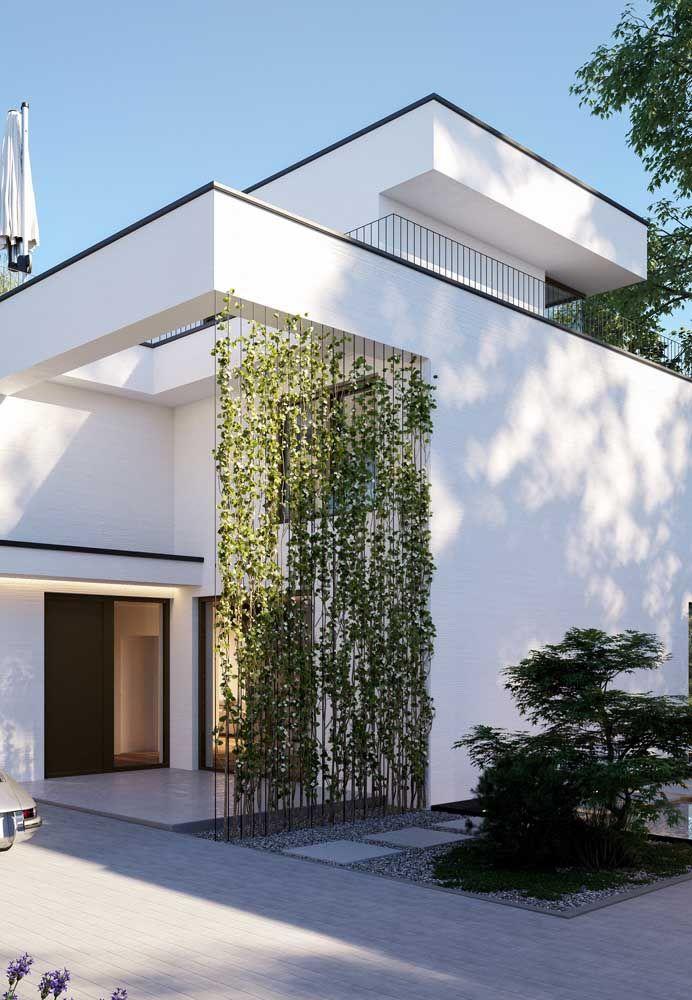 Casa moderna branca conta com o visual acinzentado da Miracema para forrar o chão