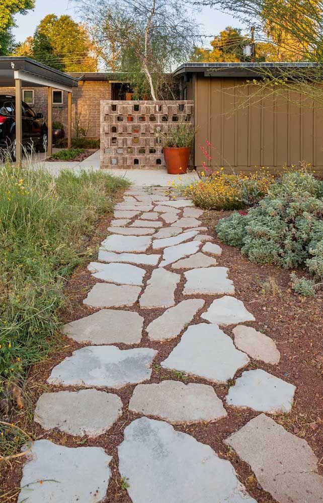 Diretamente sobre a terra, essa calçada de pedra basalto ganhou um aspecto rústico muito bonito
