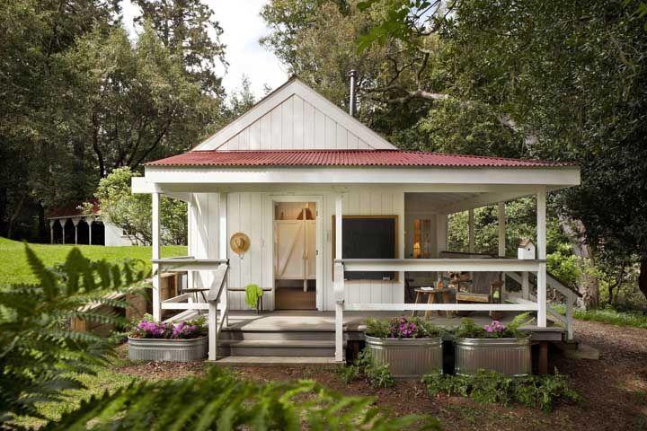 Nessa casa de estilo cottage, o telhado vermelho contrasta com o branco das paredes