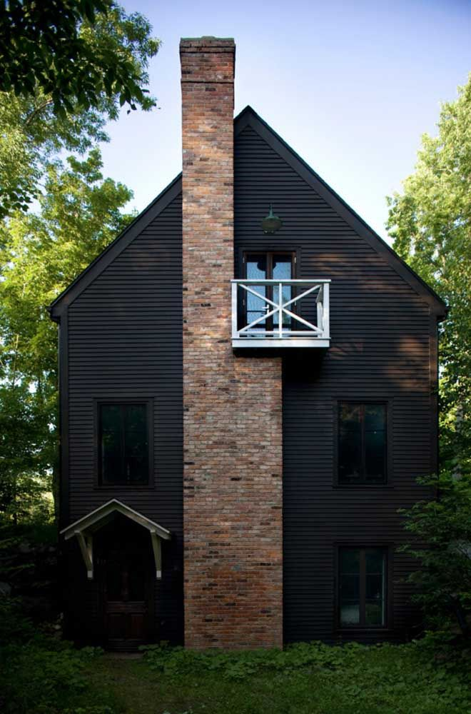 Essa casa toda preta, em meio à natureza, revela o uso da madeira e dos tijolos aparentes na fachada