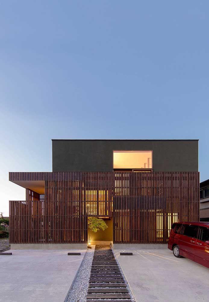 O caminho de pedras leva até a entrada da casa asiática com fachada em madeira