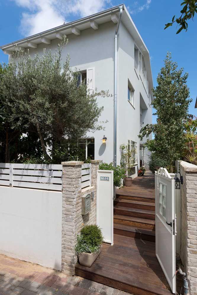 O verde do jardim forma um belo contraste com as paredes brancas da casa mediterrânea