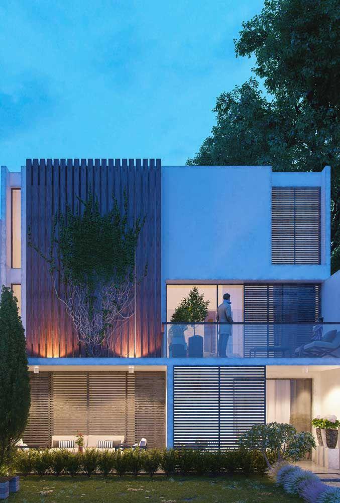 Linhas retas e puras na fachada contrastadas pelo uso conjunto de vidro, concreto e madeira