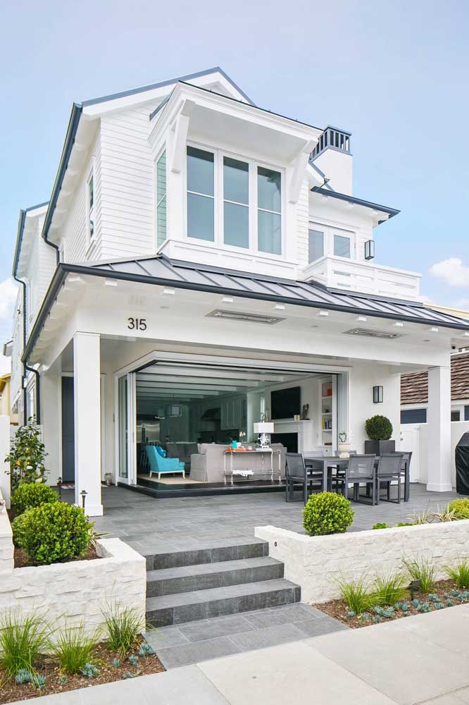 Casa de praia branca com varanda integrada à sala de estar