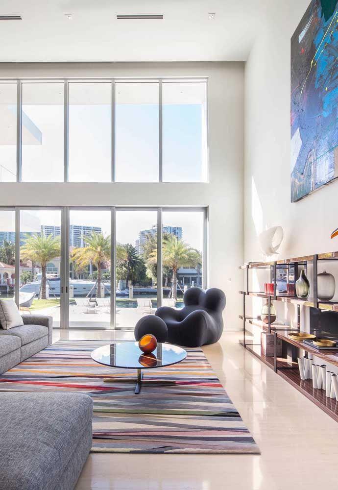 Porcelanato em tons claros ajudaram a sala ampla, com pé direito alto e grandes janelas, a aumentar o conforto do ambiente