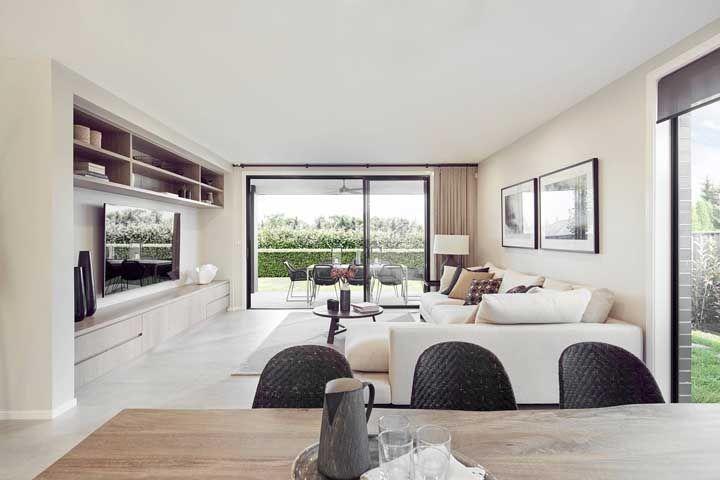 O piso porcelanato acetinado branco trouxe amplitude e iluminação extra para essa sala de estar