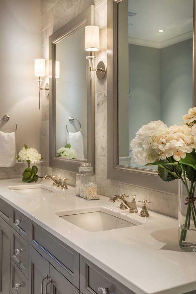 Bancada em Marmoglass branco combinada ao estilo clássico do banheiro e os detalhes da pedra na parede