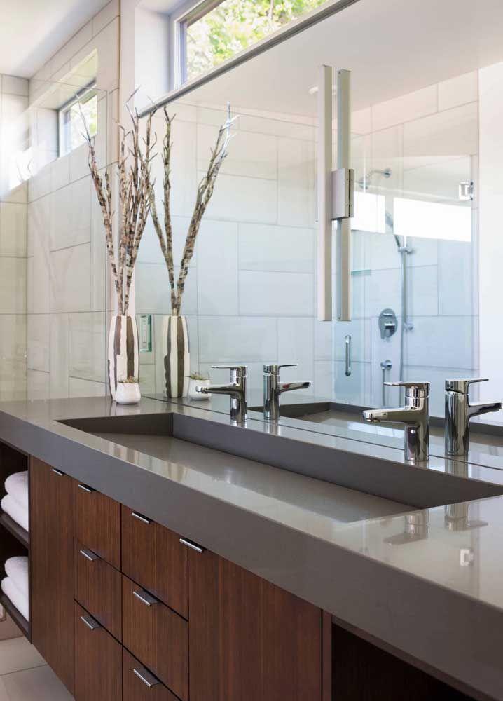A extensa bancada do banheiro ficou ainda mais bonita com o detalhe da cuba esculpida no Marmoglass