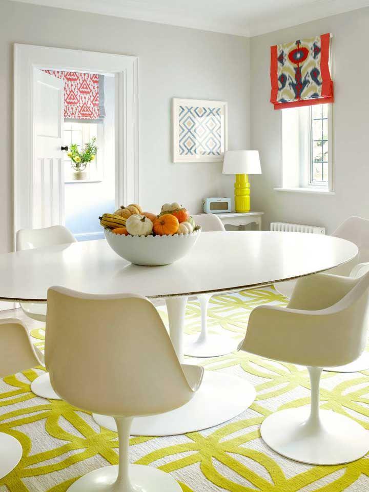 A pequena sala de jantar branca apostou em uma persiana romana marrom para criar contraste, mas sem perder a neutralidade